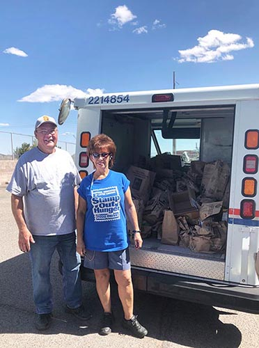 Volunteer Paul Dillion, left, and organizer Pearl take a quick photo in front of food donations.